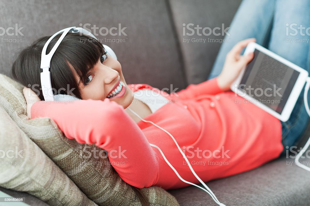Woman with headphones using a tablet stock photo