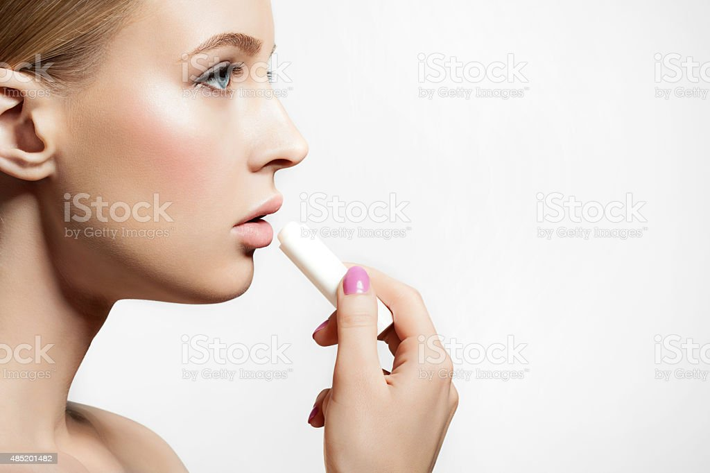 Woman with healthy skin applying a protective lip balm stock photo