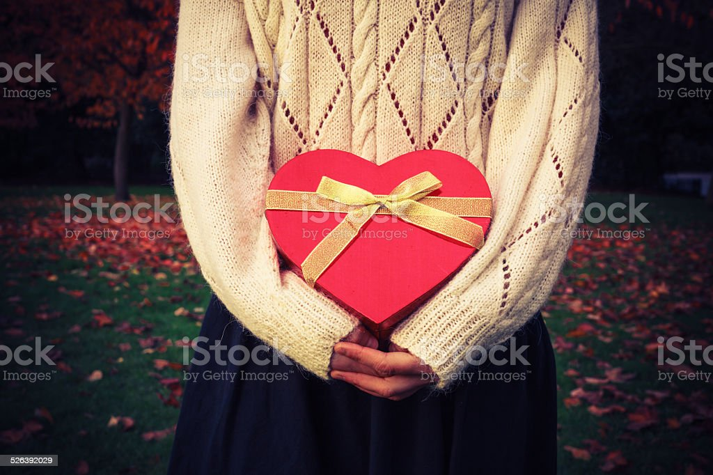 Woman with heart shaped box in park stock photo