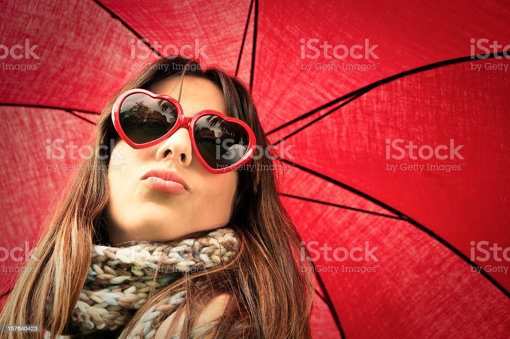 Woman with heart shaped glasses blowing a kiss stock photo