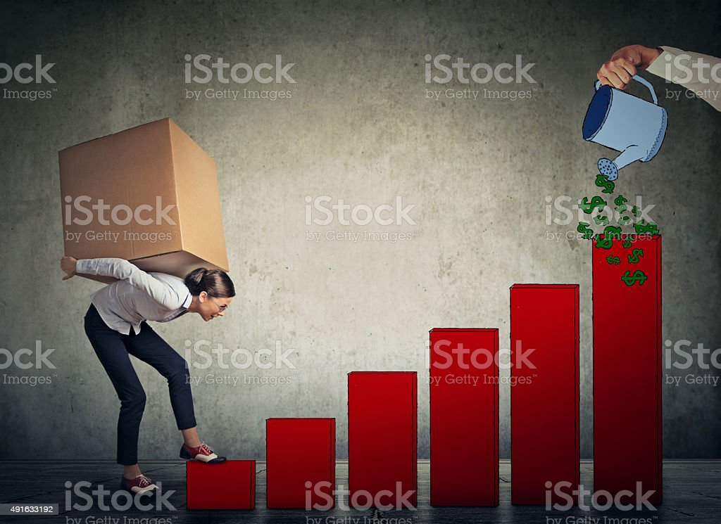 Woman with heavy box climbing up financial success ladder stock photo