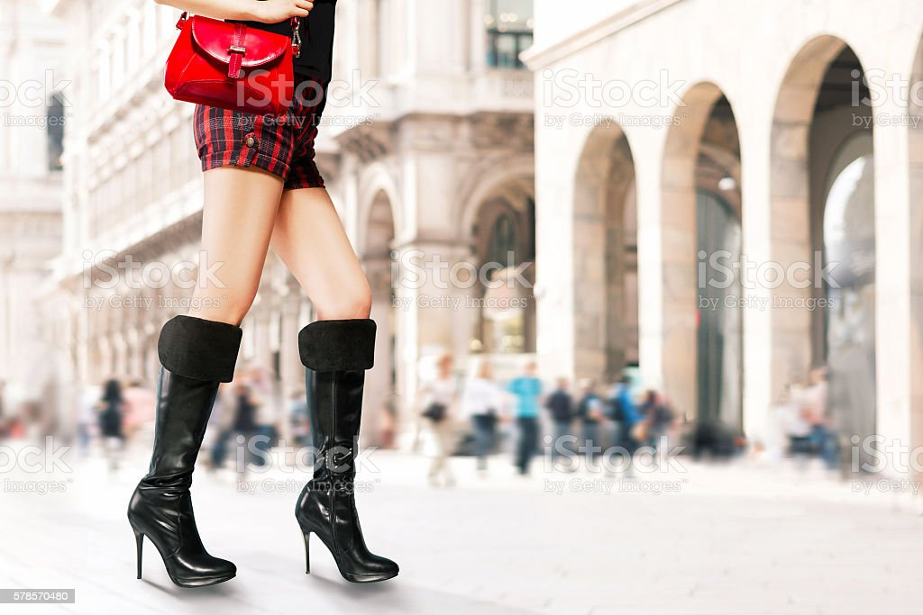 Woman with heels boots,purse,shorts walking in the city. stock photo