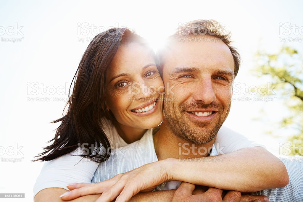 Woman with her arms wrapped around her man stock photo