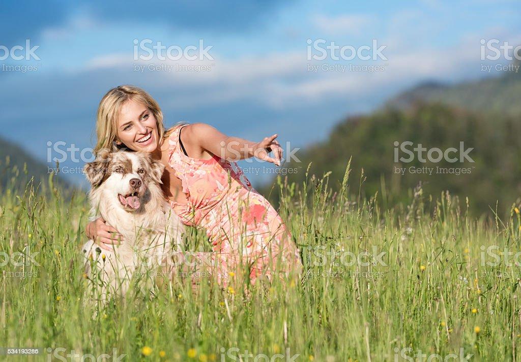 Woman with her Australian Shepherd Dog in Nature stock photo