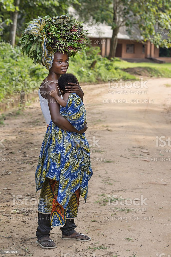 Woman with her baby carrying vegetables stock photo