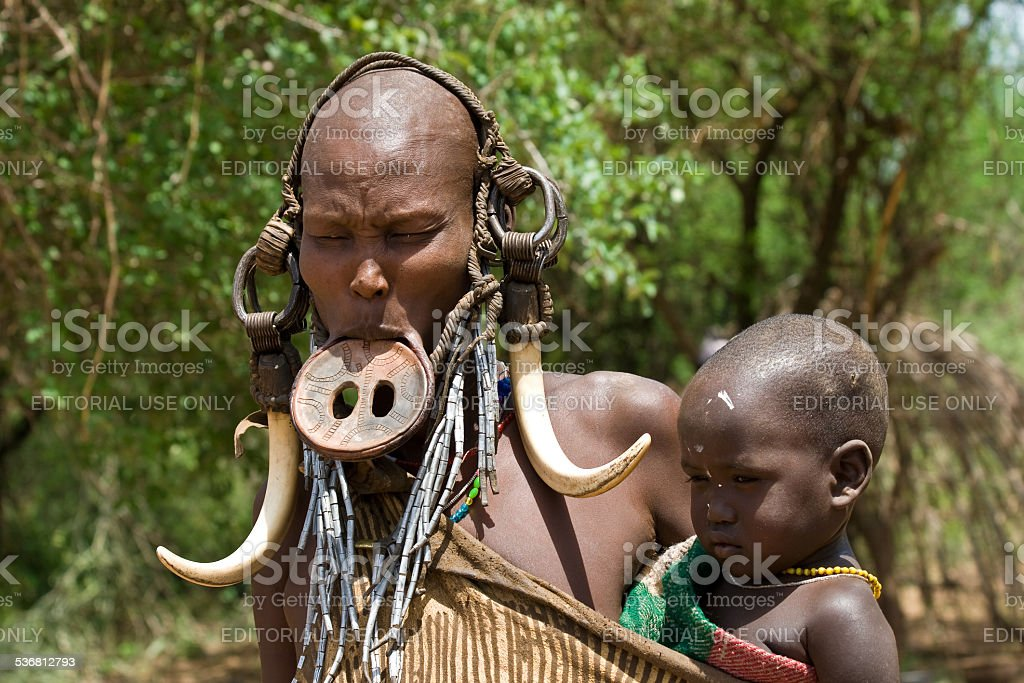 Woman with her baby of the Mursi tribe. stock photo