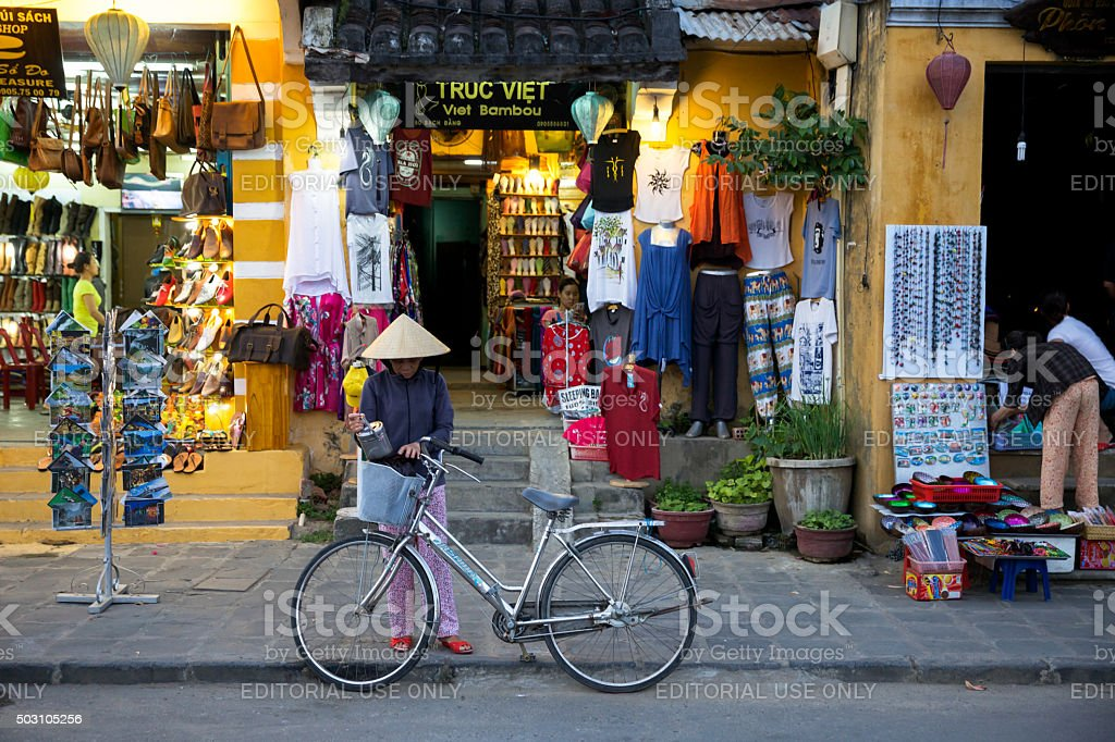 Woman with her bicycle in traditional conical hat stock photo