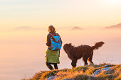 Woman with her black shepherd walking in the mountains