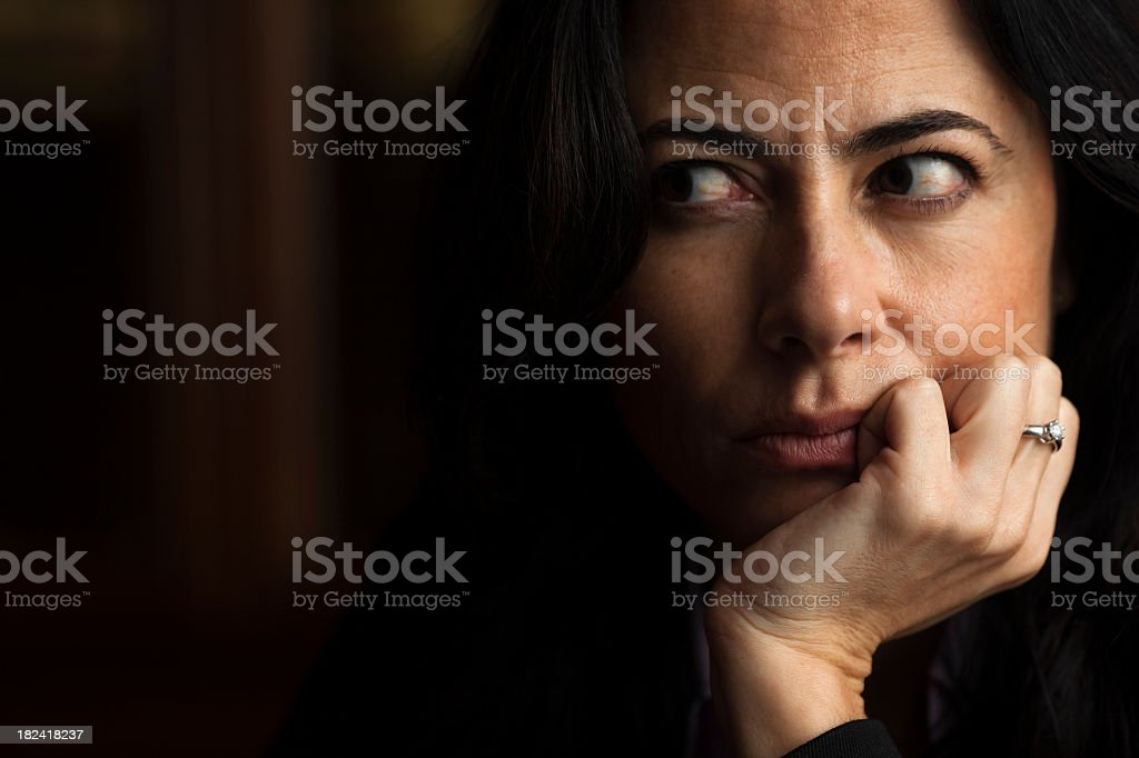 A woman with her hand on her chin cutting her eyes sideways royalty-free stock photo