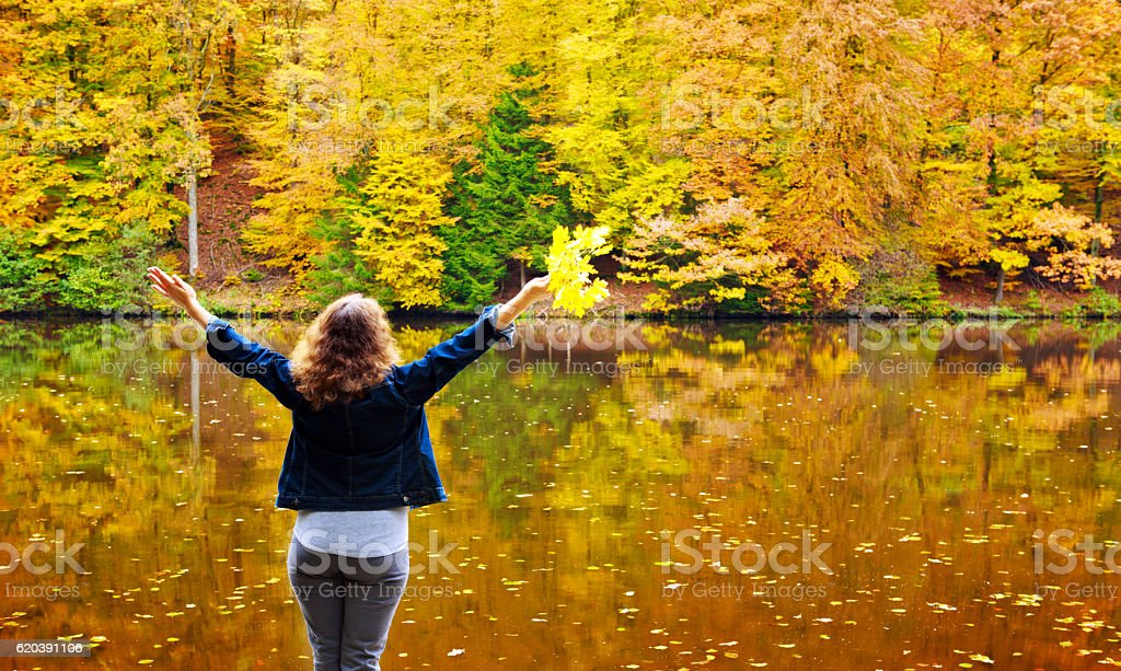 Woman with her hands raised near the beautiful autumn lake. stock photo