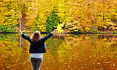 Woman with her hands raised near the beautiful autumn lake.