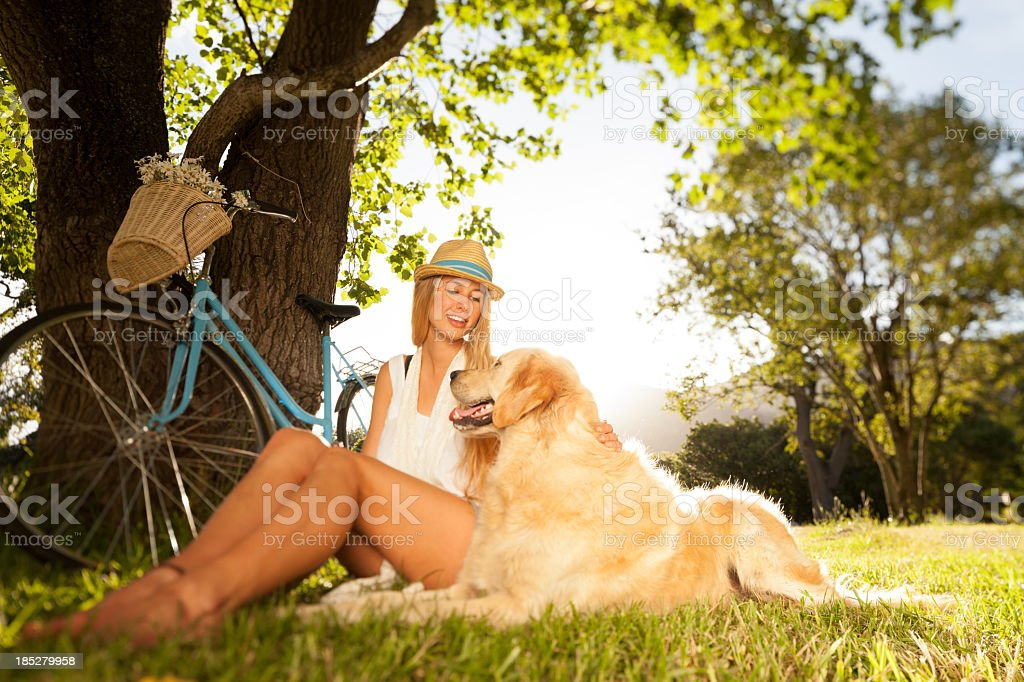 Woman With Her Pet Dog Sitting In Park royalty-free stock photo