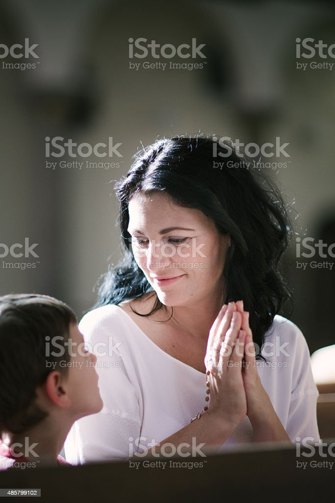 Woman with her son praying stock photo