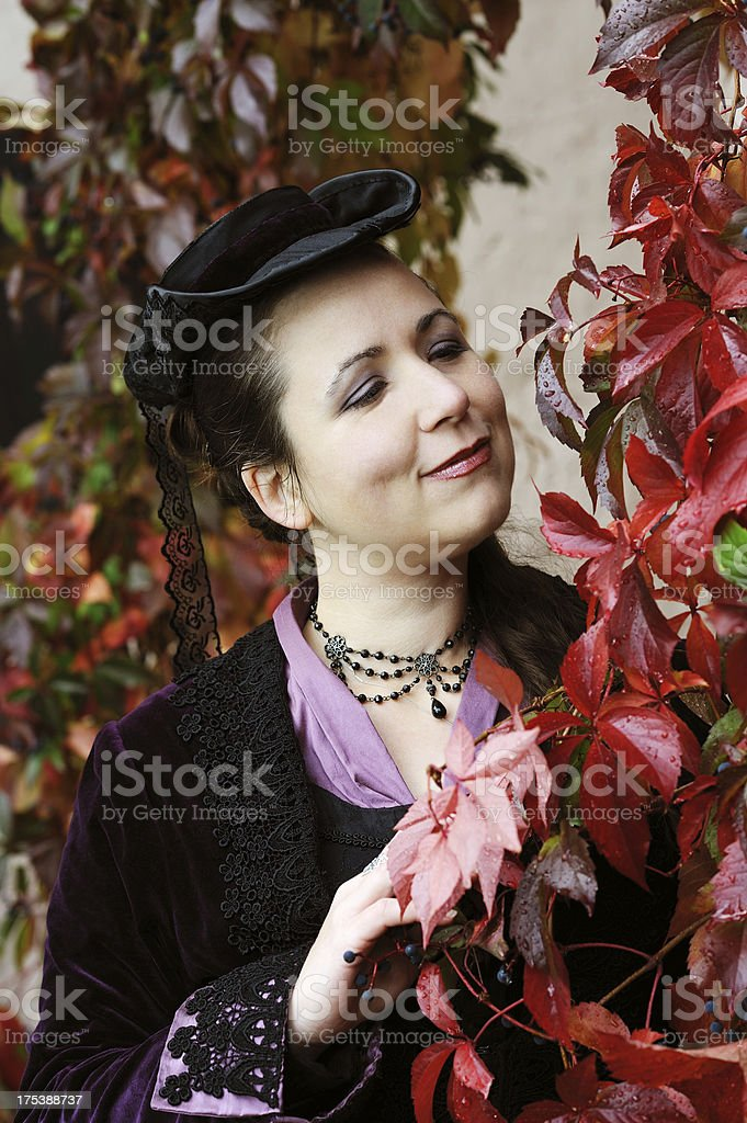 Woman with Historical Outfit looking for Red Leaves Portrait stock photo