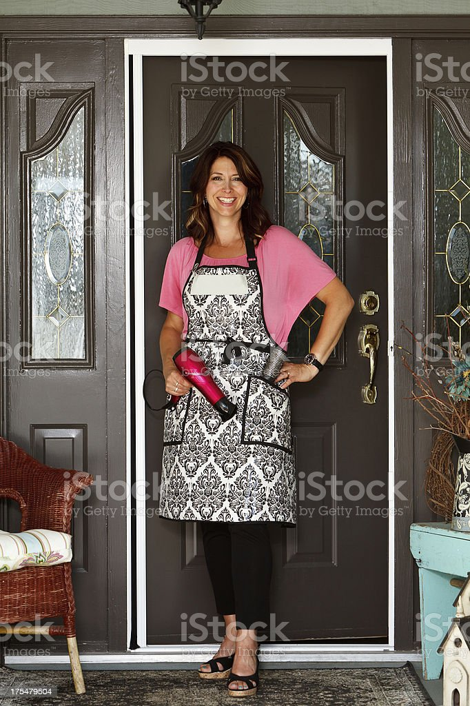 Woman with home hair salon business standing at front door royalty-free stock photo