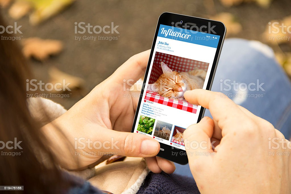 woman with influencer phone in the park stock photo