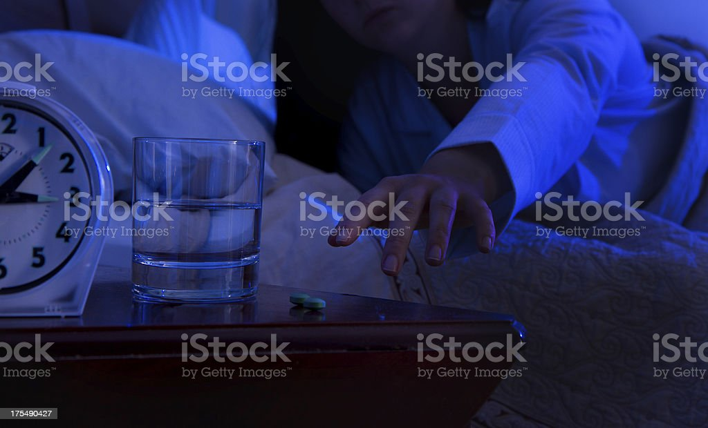 Woman With Insomnia Reaching For Sleeping Pills stock photo