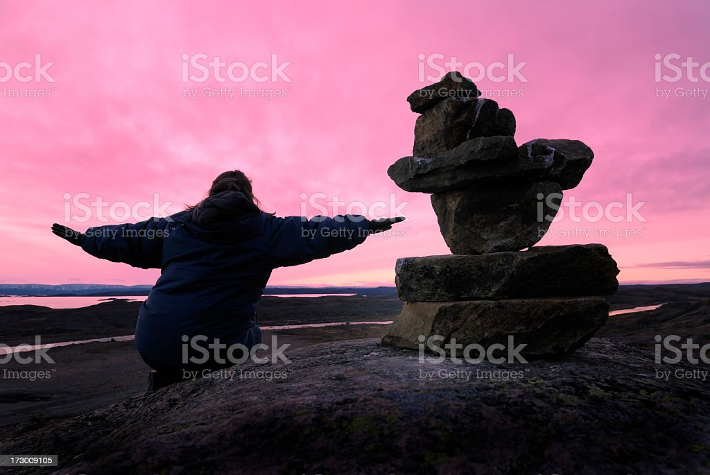 Woman with Inukshuk, Baffin Island. stock photo