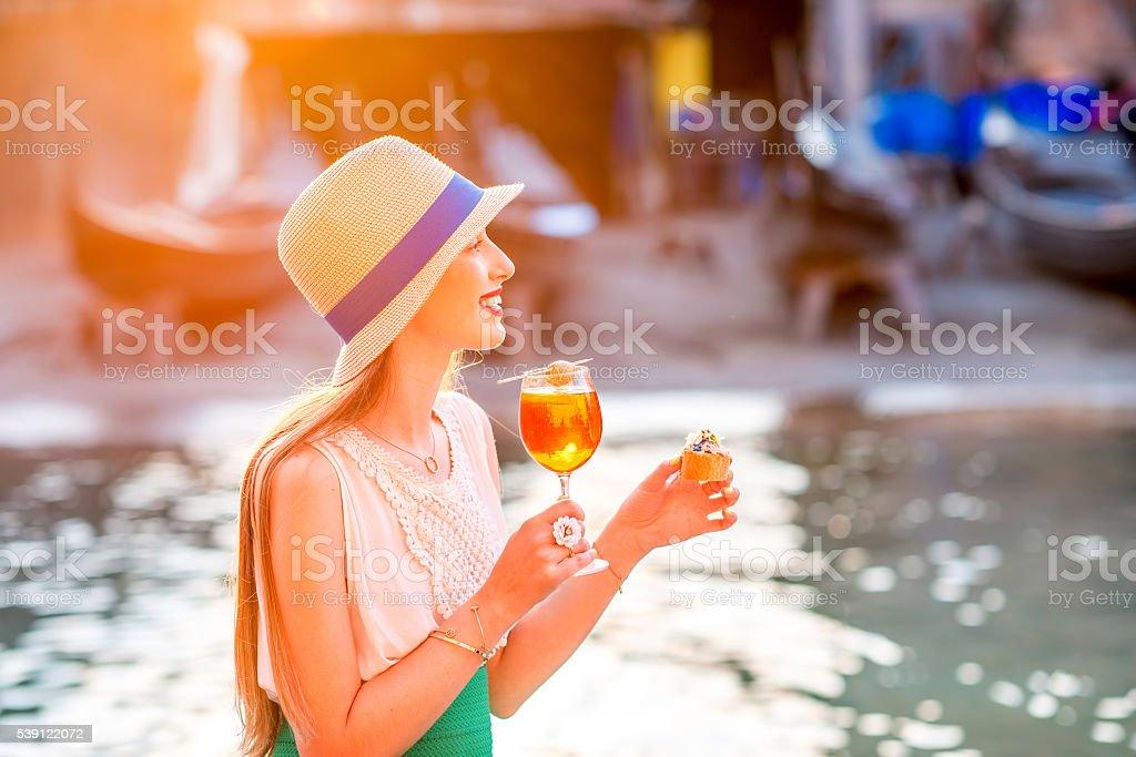 Woman with italian aperitif near the water chanal in Venice stock photo