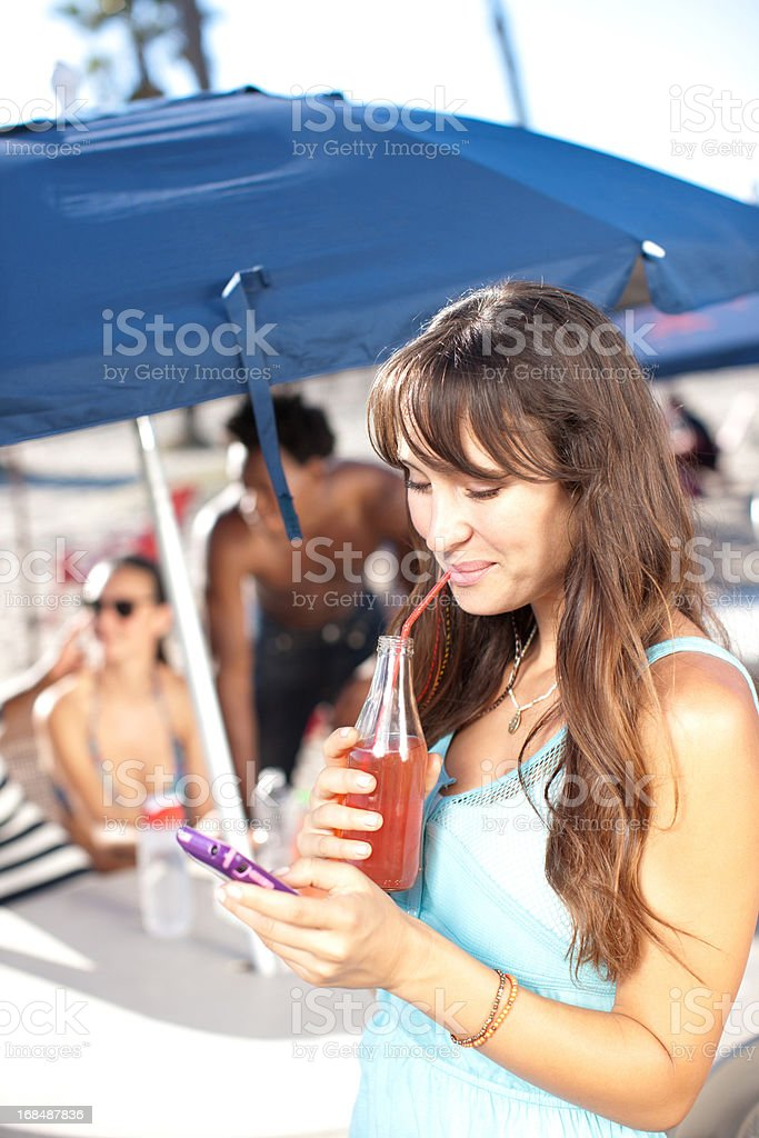 Woman with juice using cell phone outdoors royalty-free stock photo