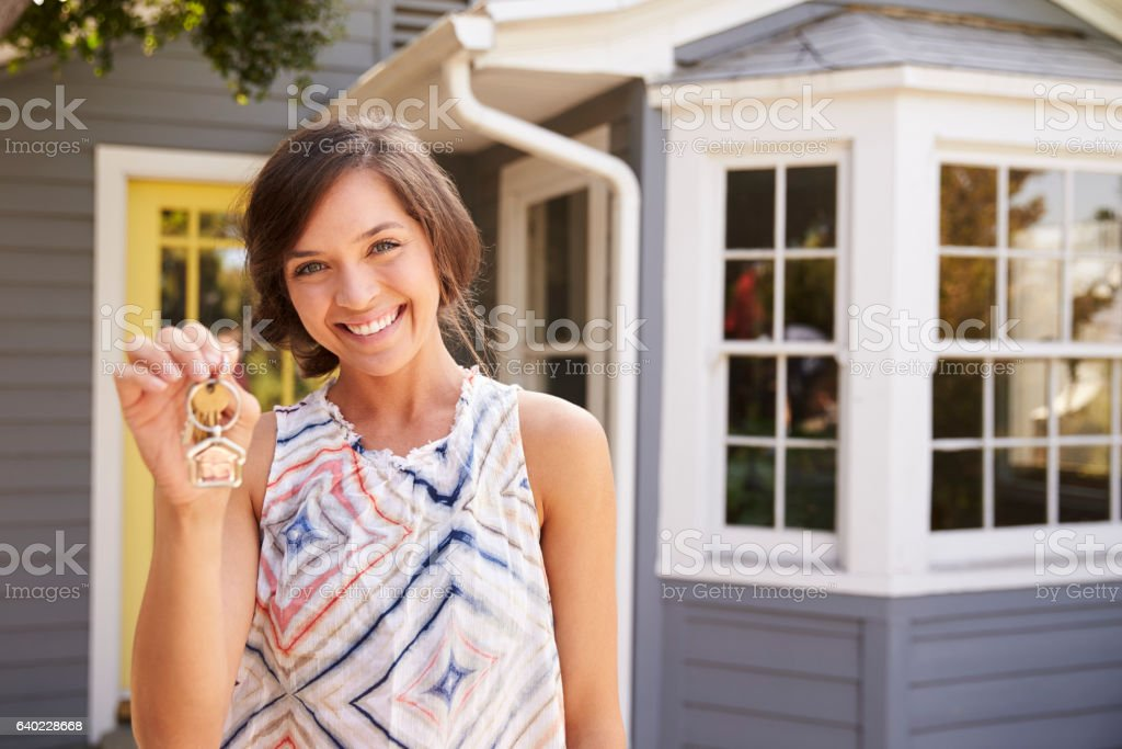 Woman With Keys Standing Outside New Home stock photo