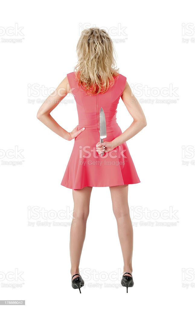woman with knife behind her back stock photo