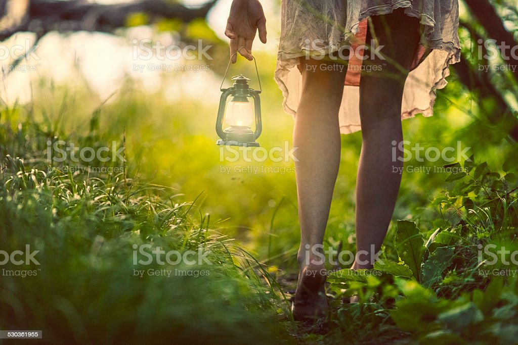 Woman with lantern in the forest stock photo