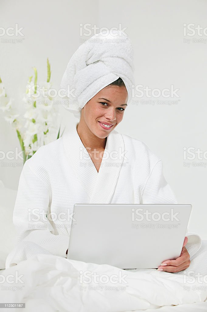 Woman with laptop and hair wrapped in towel stock photo