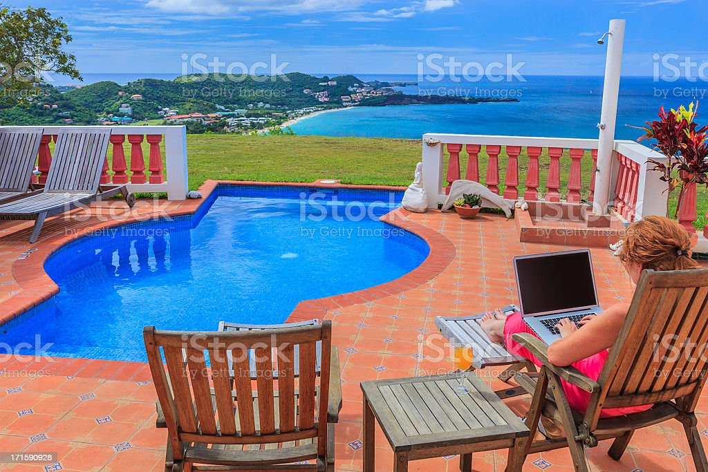 Woman with laptop at poolside stock photo