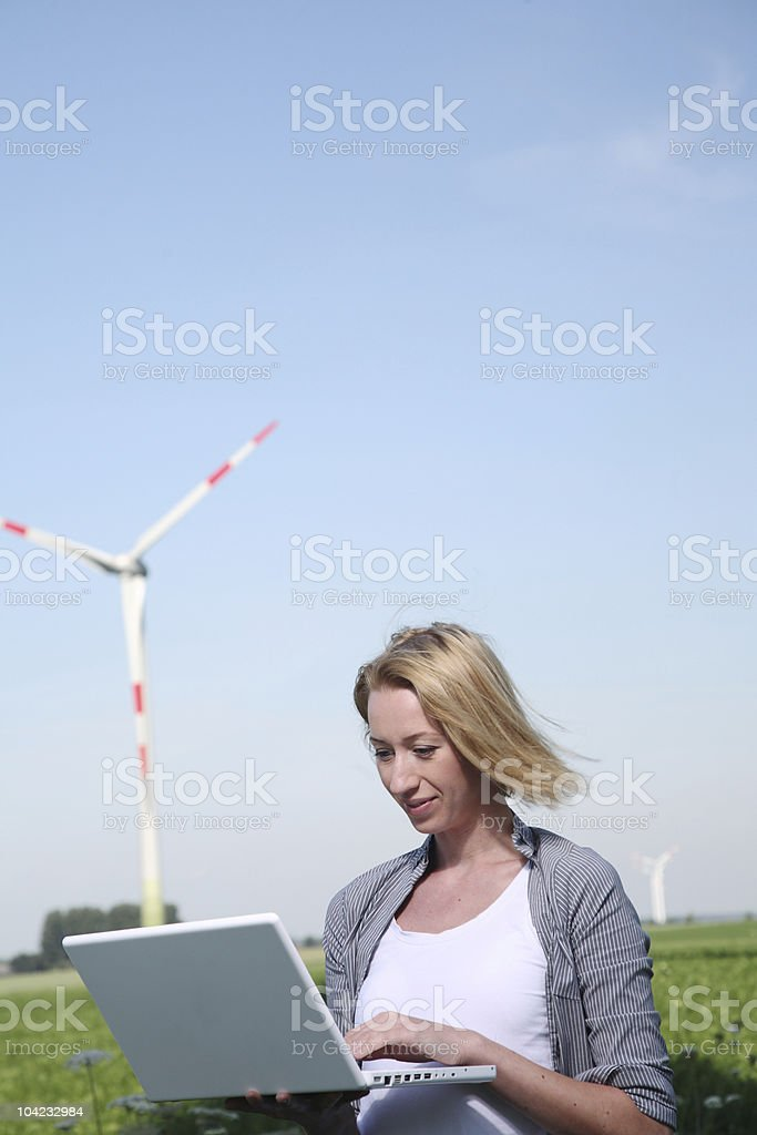 Woman with Laptop at Wind Turbine stock photo
