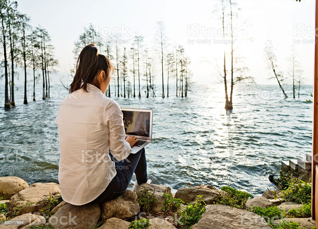 Woman with laptop by the lake stock photo