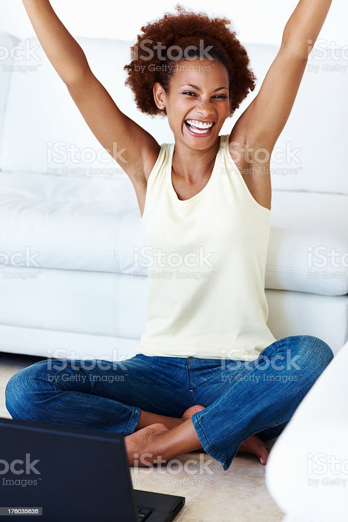 Woman with laptop cheering in success stock photo