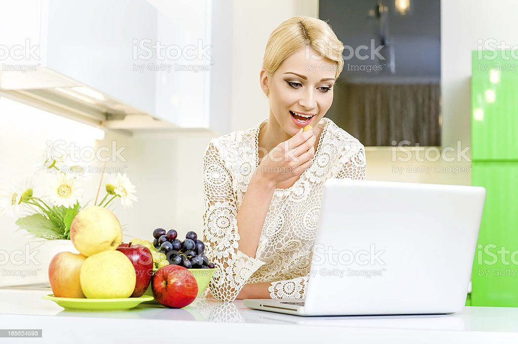 Woman with laptop computer in the kitchen royalty-free stock photo
