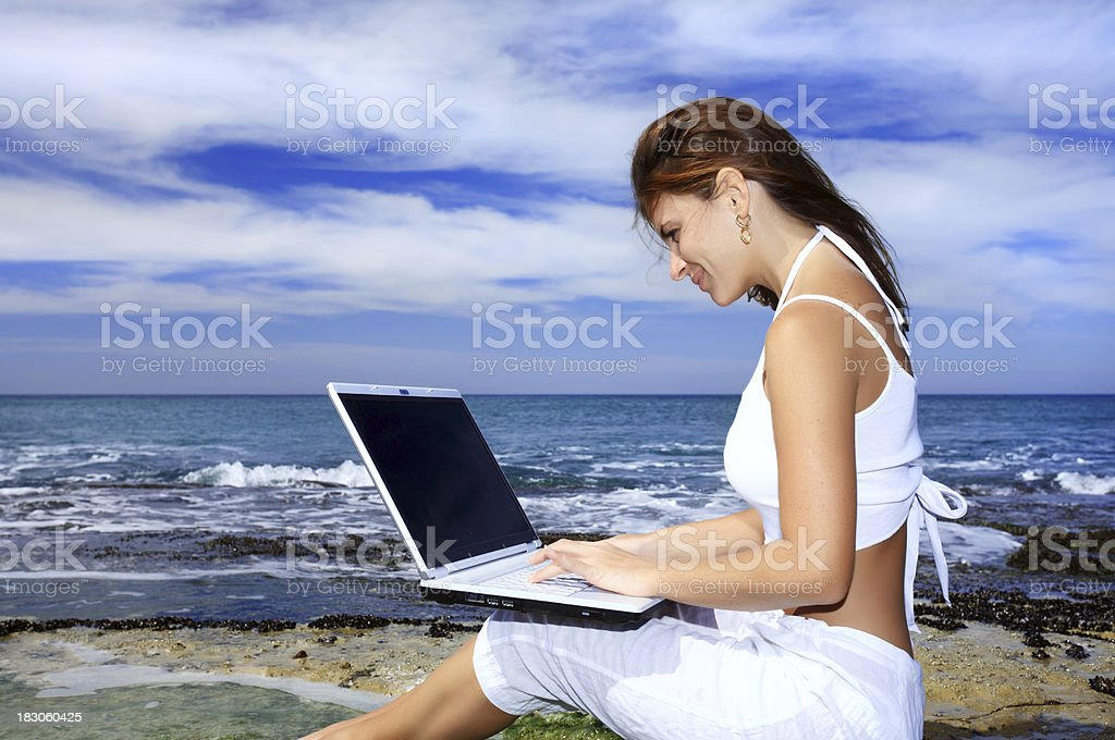 Woman with laptop computer on the beach. royalty-free stock photo