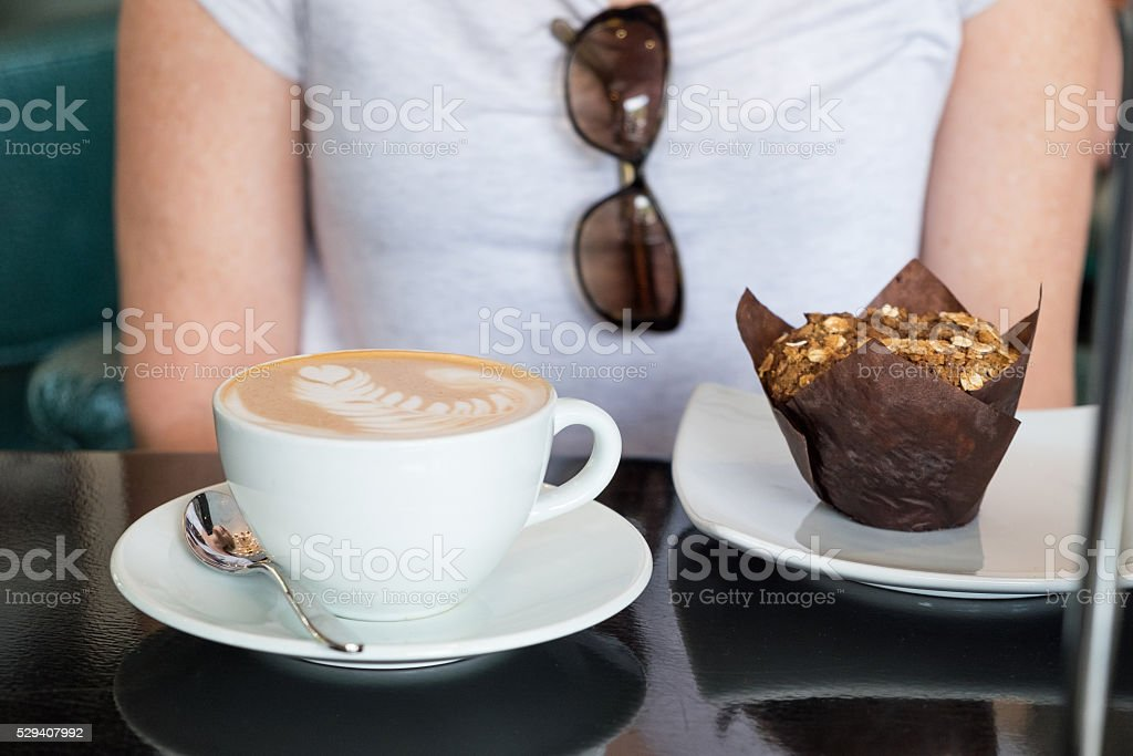 Woman With Latte and Bran Muffin stock photo