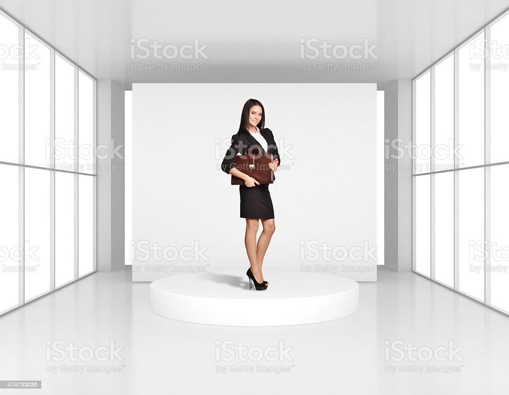 Woman with leather briefcase standing on the podium in bright stock photo