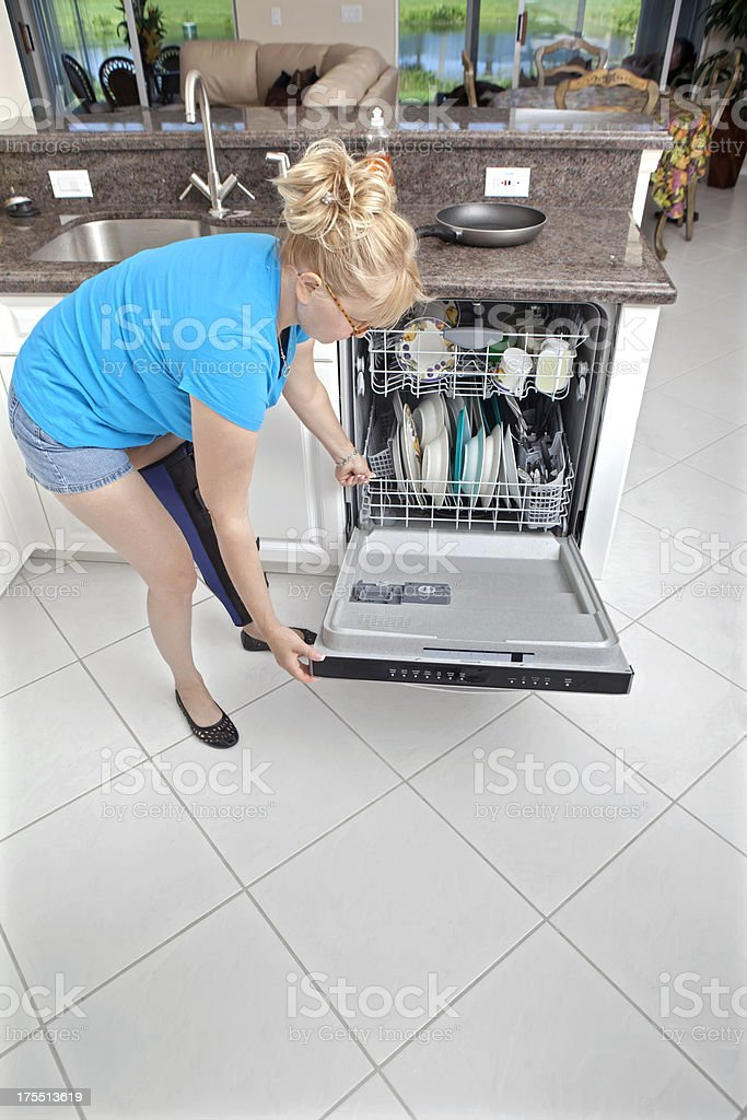 Woman with leg cast trying to do dishes royalty-free stock photo