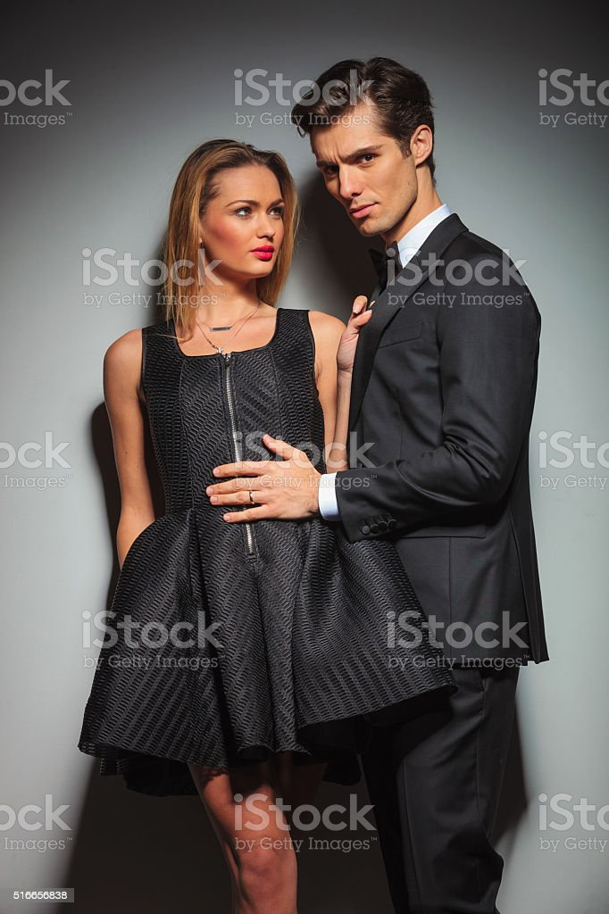 woman with legs crossed pulling businessman's jacket stock photo