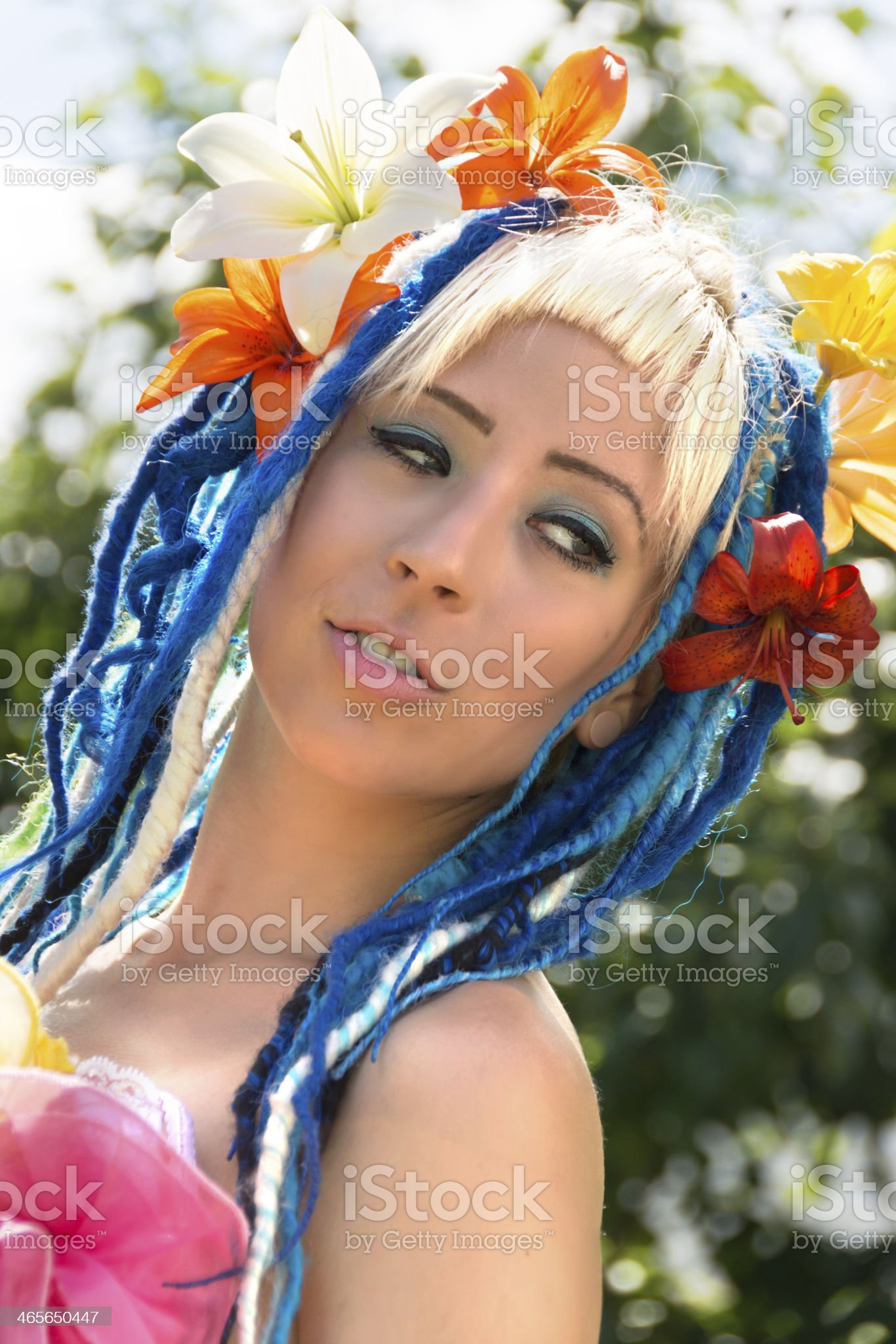 Woman with lilies in blue dreads head angled. royalty-free stock photo