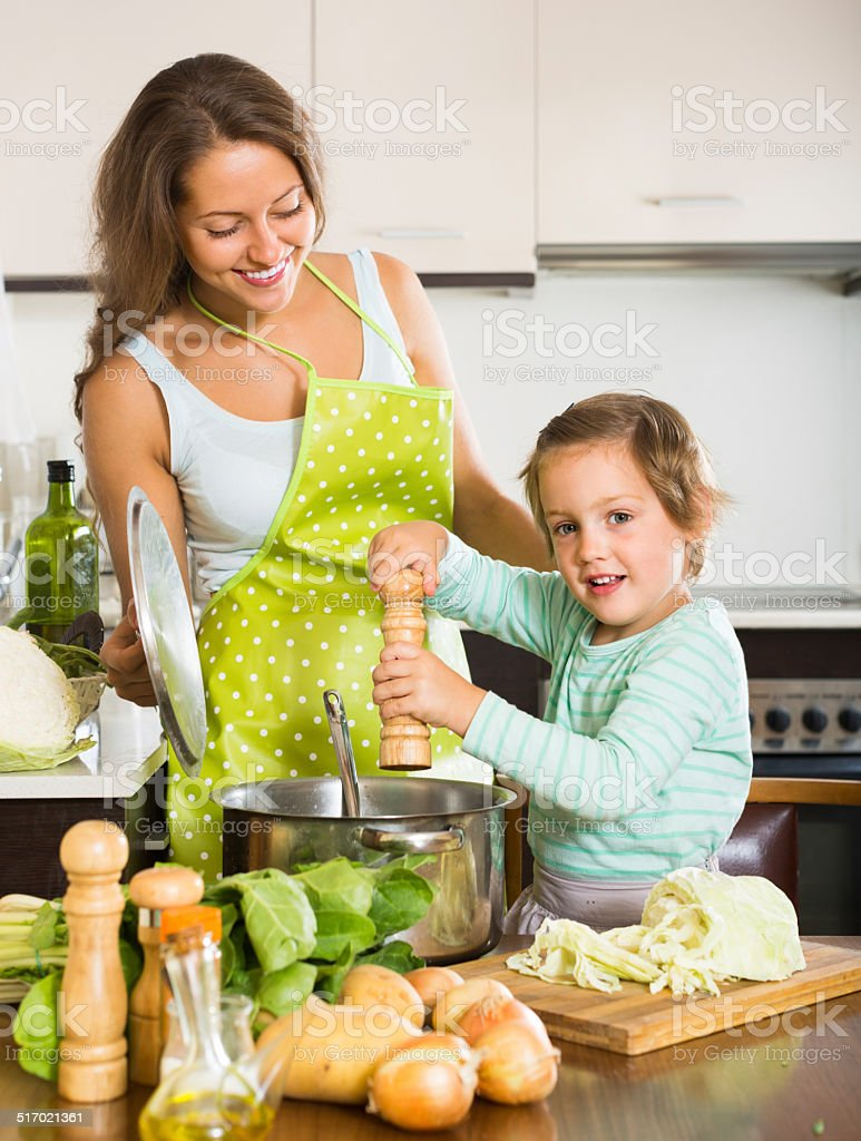 Woman with little girl cooking at home stock photo