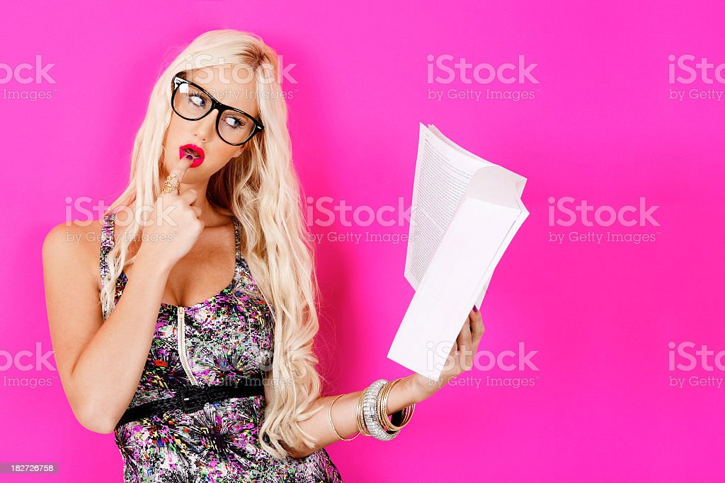 Woman with long blonde hair and glasses studying from a book stock photo