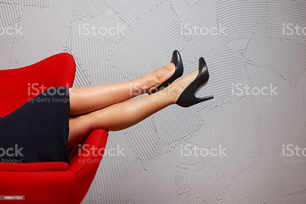 woman with long legs resting in a red armchair stock photo