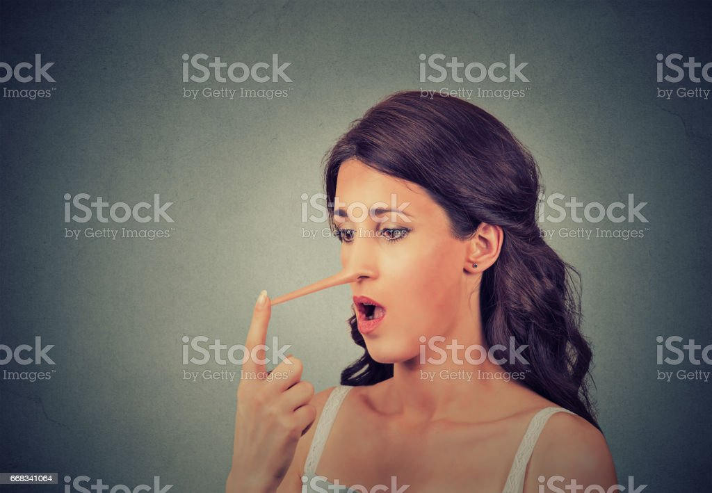 Woman with long nose isolated on grey wall background. Liar concept stock photo