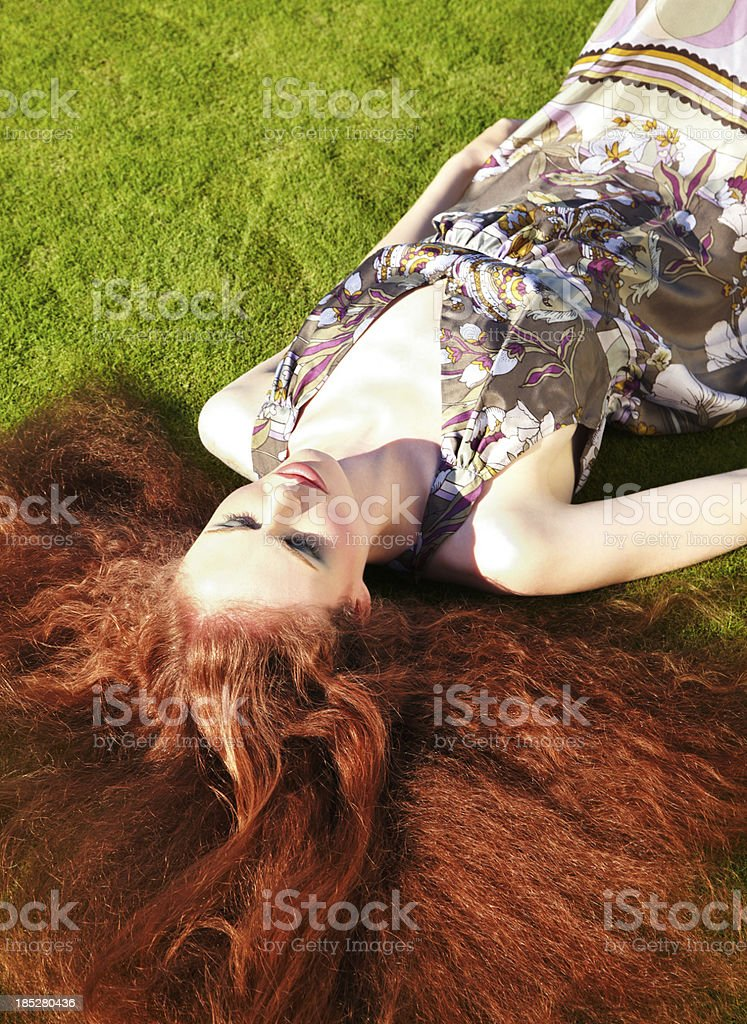 Woman with long red hair lying in grass wearing dress stock photo