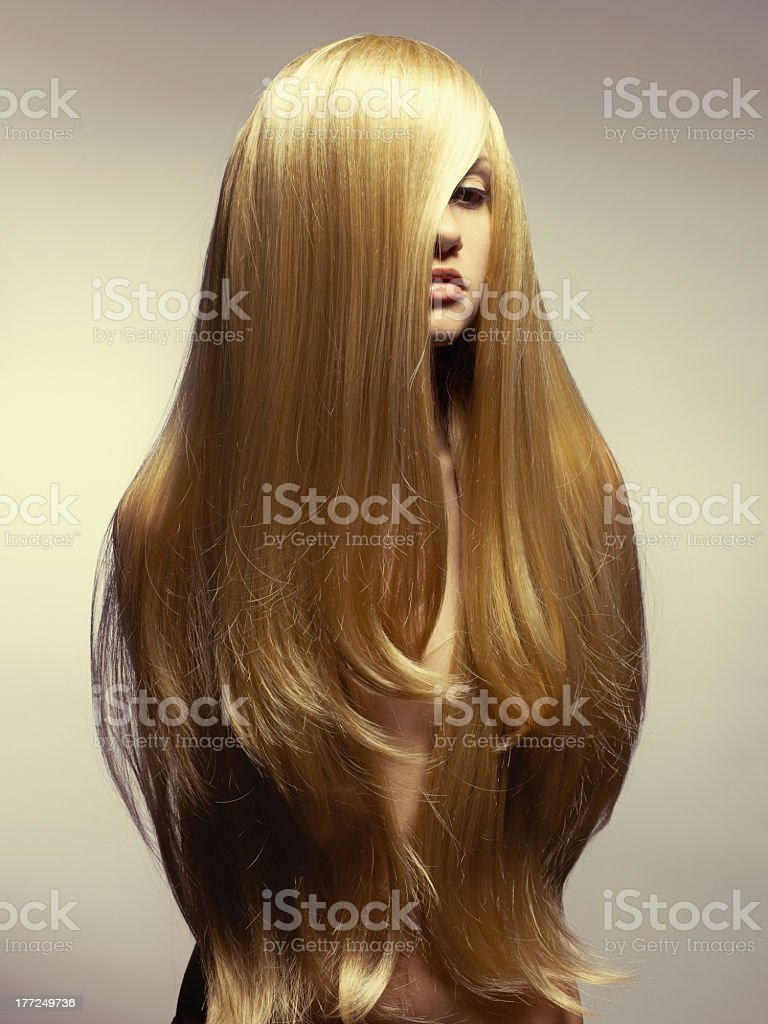 Woman with long, straight blonde hair combed forward stock photo