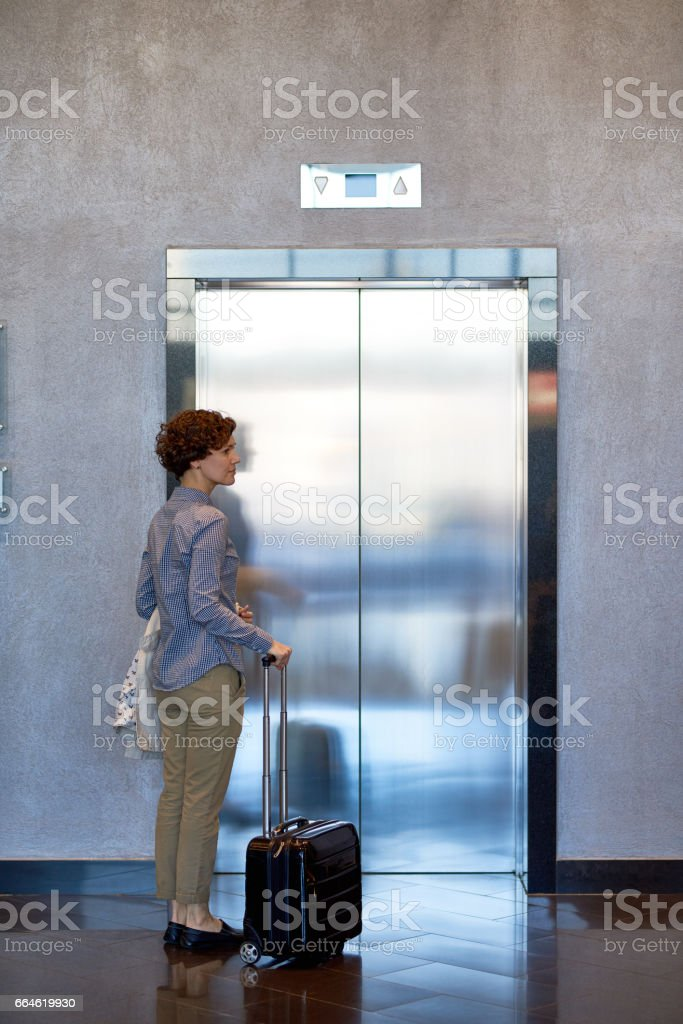 Woman with luggage in hotel stock photo