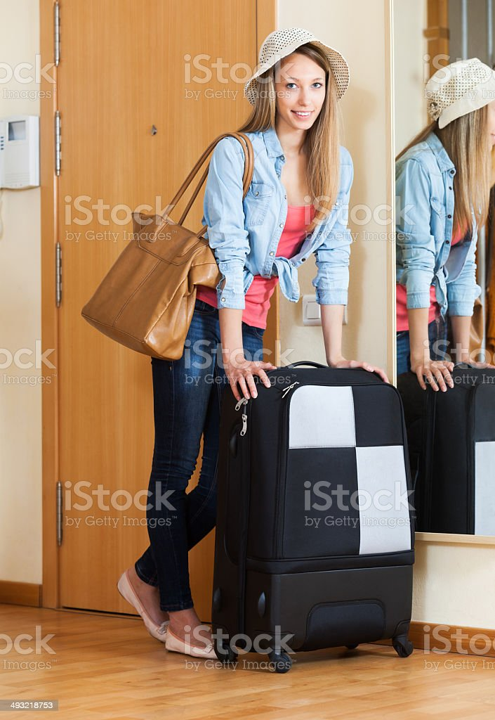 Woman with luggage near door stock photo