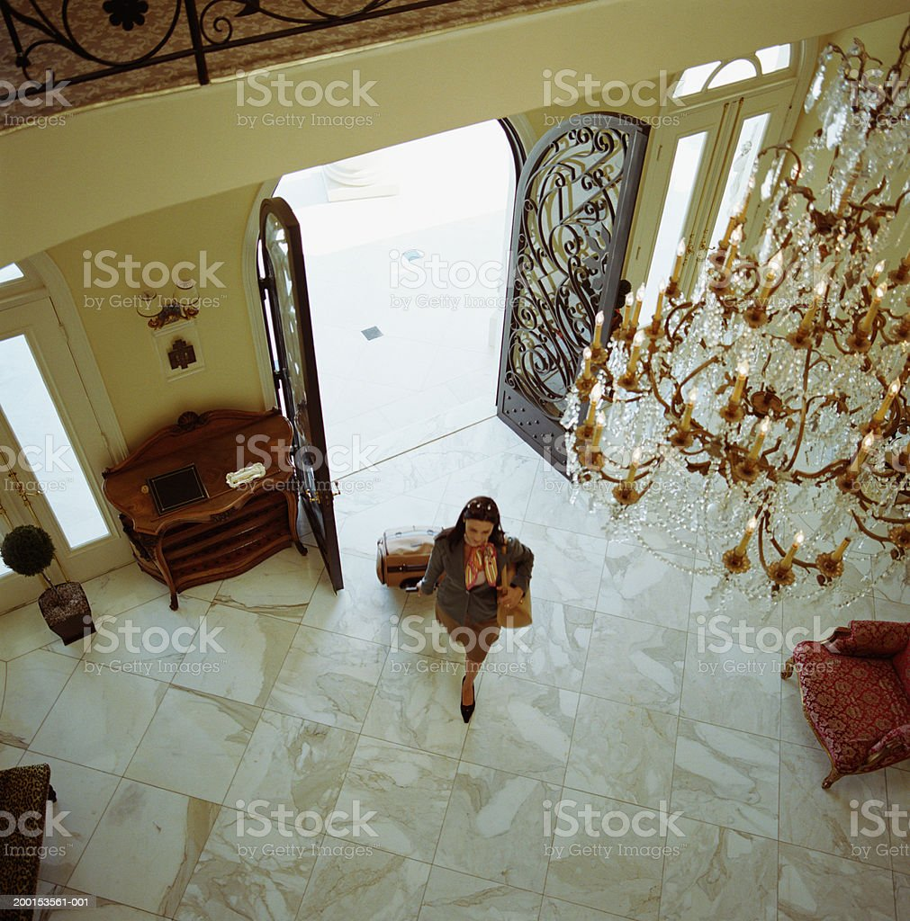 Woman with luggage, walking into hotel, elevated view stock photo