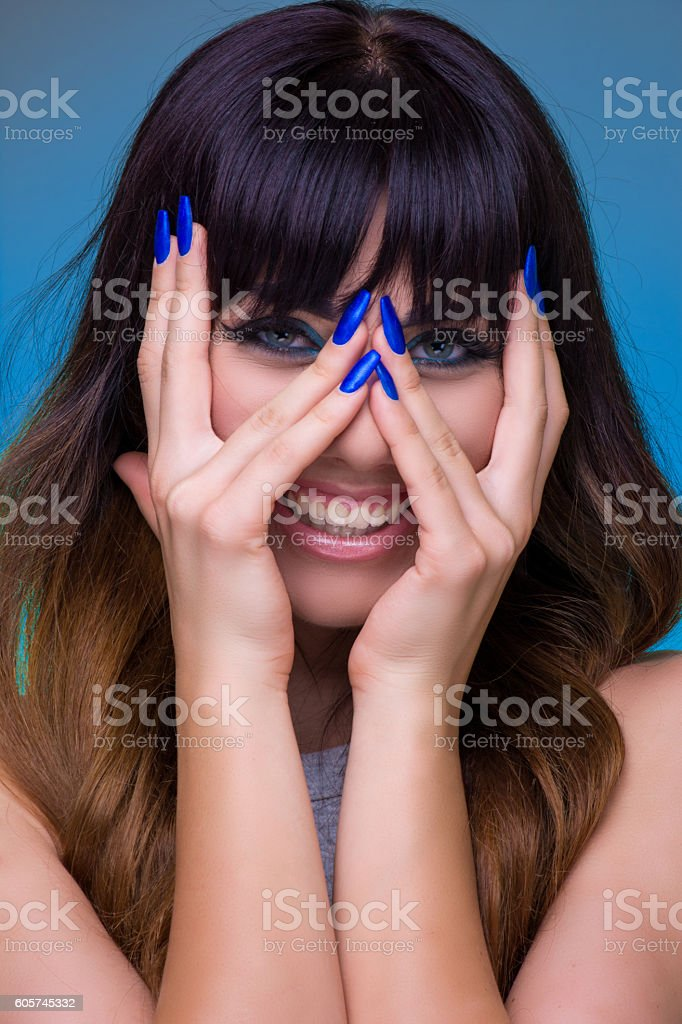 Woman with make-up peeking through fingers stock photo