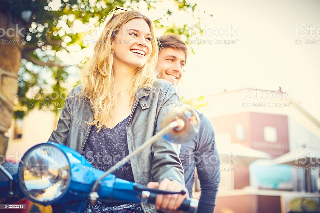 Woman with man riding scooter in city stock photo
